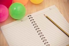Dra tillbaka till skolabakgrund med anteckningsboken och den färgrika bollen, vinta Arkivfoto