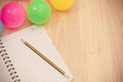 Dra tillbaka till skolabakgrund med anteckningsboken och den färgrika bollen, vinta Arkivbild