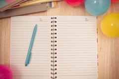 Dra tillbaka till skolabakgrund med anteckningsboken och den färgrika bollen, vinta Arkivbilder