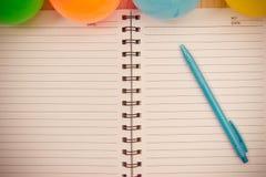 Dra tillbaka till skolabakgrund med anteckningsboken och den färgrika bollen, vinta Royaltyfria Foton
