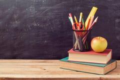 Dra tillbaka till skolabakgrund med böcker, blyertspennor och äpplet Arkivfoto