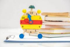 Dra tillbaka till skolabakgrund med böcker och ringklockan över den svart tavlan `-klocka för nolla 12 Begrepp för Tid ledning Nä Royaltyfria Foton