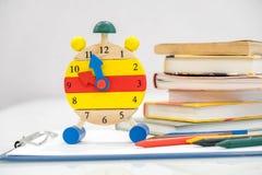 Dra tillbaka till skolabakgrund med böcker och ringklockan över den svart tavlan `-klocka för nolla 12 Begrepp för Tid ledning Nä Arkivfoton