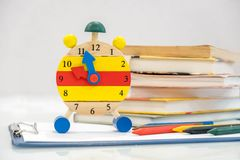 Dra tillbaka till skolabakgrund med böcker och ringklockan över den svart tavlan `-klocka för nolla 12 Begrepp för Tid ledning Nä Royaltyfria Bilder