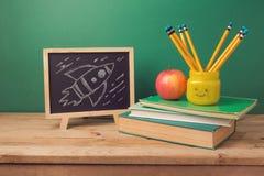 Dra tillbaka till skolabakgrund med böcker, blyertspennor i emojikruset, äpplet, svart tavla, och raket skissar Arkivfoto