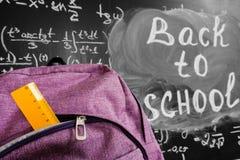 Dra tillbaka till skolabakgrund med den purpurfärgade skolapåsen med den gula linjalen och titel`en tillbaka till skola`- och mat Arkivfoton