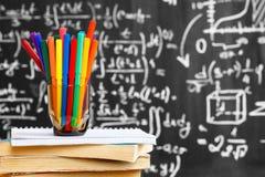 Dra tillbaka till skolabakgrund med färgrika blyertspennor på böckerna och anteckningsboken och titel`en tillbaka till skola` som Royaltyfri Bild
