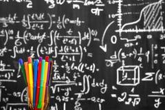 Dra tillbaka till skolabakgrund med färgrika filtpennor och suddiga matematikformler som är skriftliga vid vit krita på den svart Arkivbild
