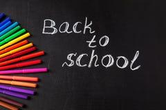 Dra tillbaka till skolabakgrund med färgrika pennor för filtspetsen och betitla tillbaka till skolan som är skriftlig vid vit kri Arkivfoto