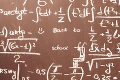 Dra tillbaka till skolabakgrund med matematikformler är skriftligt vid vit krita på den bruna svart tavlan Arkivbild