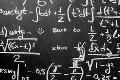 Dra tillbaka till skolabakgrund med matematikformler är skriftligt vid vit krita på den svarta svart tavlan Royaltyfria Bilder