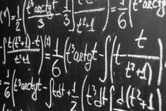 Dra tillbaka till skolabakgrund med matematikformler är skriftligt vid vit krita på den svarta svart tavlan Arkivfoto