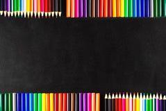 Dra tillbaka till skolabakgrund med mycket färgrika tuschpennor och färgrika blyertspennor på den svart skrapade chalkboardnen Arkivbild