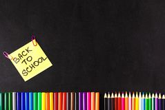 Dra tillbaka till skolabakgrund med mycket färgrika tuschpennor och färgrika blyertspennor, titlar tillbaka till skolan på guling Arkivfoton