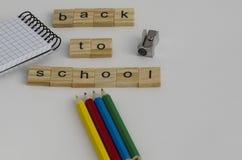 Dra tillbaka till skolabakgrund med pennor, notepaden, vässare a fotografering för bildbyråer