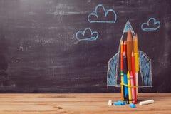 Dra tillbaka till skolabakgrund med raket som göras från färgade blyertspennor Fotografering för Bildbyråer