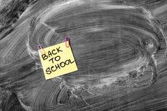 Dra tillbaka till skolabakgrund med titel tillbaka till skolan på gult stycke av papper på den svart tavlan för skolan Arkivfoto