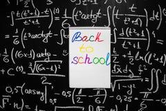 Dra tillbaka till skolabakgrund med titel tillbaka till skolan som är skriftlig på den vita sidan av anteckningsboken på den svar Fotografering för Bildbyråer