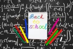 Dra tillbaka till skolabakgrund med titel tillbaka till skolan som är skriftlig på den vita sidan av anteckningsboken på den svar Royaltyfri Fotografi