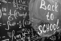 Dra tillbaka till skolabakgrund med titel` tillbaka till skola`, och matematikformler är skriftliga vid vit krita på den svarta s Arkivbild