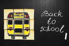 Dra tillbaka till skolabakgrund med titel` tillbaka till skola`- och `-skolbuss` som är skriftlig på de gula styckena av papper Royaltyfria Bilder