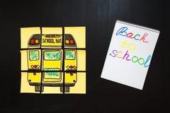 Dra tillbaka till skolabakgrund med titel` tillbaka till skola`- och `-skolbuss` som är skriftlig på de gula styckena av papper Royaltyfri Fotografi