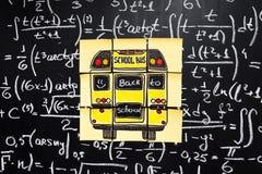 Dra tillbaka till skolabakgrund med titel` tillbaka till skola`- och `-skolbuss` som är skriftlig på de gula styckena av papper Royaltyfria Foton