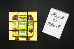 Dra tillbaka till skolabakgrund med titel` tillbaka till skola`- och `-skolbuss` som är skriftlig på de gula styckena av papper o Arkivbild
