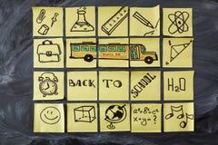 Dra tillbaka till skolabakgrund med titel tillbaka till skola-, skolbuss- och skolaattribut som är skriftliga på styckena av papp Royaltyfri Fotografi
