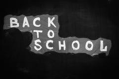 Dra tillbaka till skolabakgrund med titel` tillbaka till skola` som är skriftlig vid vit krita på den svarta svart tavlan Arkivfoton