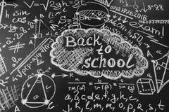 Dra tillbaka till skolabakgrund med titel tillbaka till skolan och formler som är skriftliga vid krita på den svart tavlan Arkivfoto
