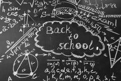 Dra tillbaka till skolabakgrund med titel tillbaka till skolan och formler som är skriftliga vid vit krita på den svart tavlan Royaltyfria Foton