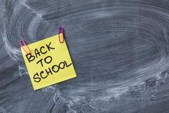 Dra tillbaka till skolabakgrund med titel tillbaka till skolan på gult stycke av papper på den svart tavlan för skolan Arkivbilder