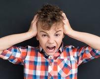 Dra tillbaka till skolabegreppet - chockad ung pojke på den svarta chalkboaen Arkivfoton