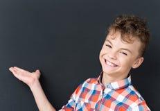 Dra tillbaka till skolabegreppet - den lyckliga pojken som ser kameran arkivfoto