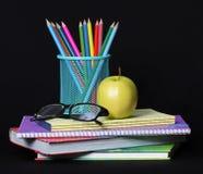 Dra tillbaka till skolabegreppet. Ett äpple, färgade blyertspennor och exponeringsglas på högen av böcker över svart Royaltyfri Foto