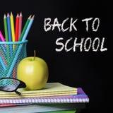 Dra tillbaka till skolabegreppet. Ett äpple, färgade blyertspennor och exponeringsglas på högen av böcker över svart bakgrund Arkivfoton