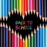 Dra tillbaka till skolabegreppet. Färgrika blyertspennor som är ordnade som hjärta på svart bakgrund. Arkivbilder