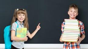 Dra tillbaka till skolabegreppet - flickan och pojken med böcker arkivbilder