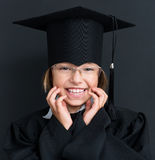Dra tillbaka till skolabegreppet - flickan som bär den svarta avläggande av examenkappan Royaltyfri Foto