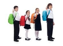 Dra tillbaka till skolabegreppet med lyckliga ungar som ger tummar upp tecken Royaltyfria Bilder