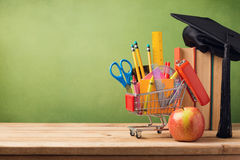 Dra tillbaka till skolabegreppet med shoppingvagnen, böcker och avläggande av examenhatten Arkivfoto