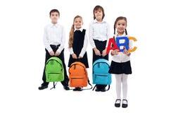Dra tillbaka till skolabegreppet med ungar som rymmer skolväskor Arkivfoton