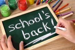 Dra tillbaka till skolabegreppet, ord som är skriftliga på den lilla svart tavla Royaltyfri Fotografi