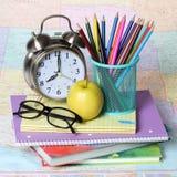 Dra tillbaka till skolabegreppet. äpple, färgade blyertspennor, exponeringsglas och ringklocka på högen av böcker över översikten Arkivfoton