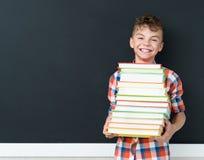 Dra tillbaka till skolabegreppet - skolpojke med böcker Royaltyfria Foton