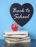 Dra tillbaka till skolahjärtasvart tavla med det röda äpplet och bunten av böcker Arkivfoto