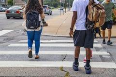 Dra tillbaka till skolan - baksidorna av högskolestudenter som korsar stads- övergångsställe med ryggsäckar - etnisk mångfald och arkivbilder