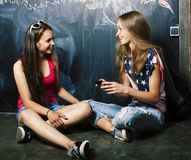 Dra tillbaka till skolan efter sommarsemestrar, två tonåriga verkliga flickor i cl royaltyfria bilder