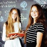 Dra tillbaka till skolan efter sommarsemestrar, två tonåriga verkliga flickor i klassrum med svart tavla som tillsammans målas, d Royaltyfri Foto